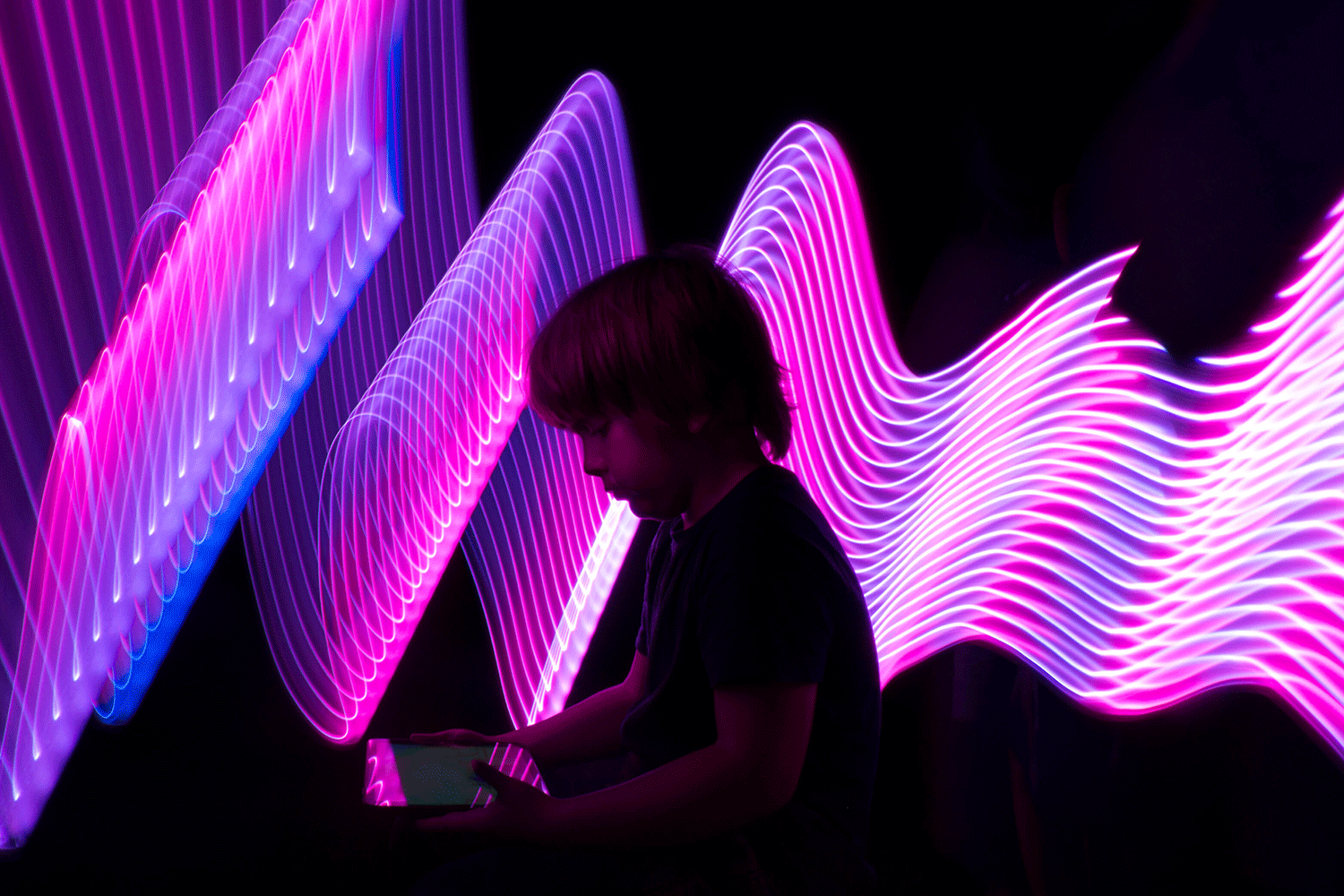 Boy with tablet in front of neon light wall