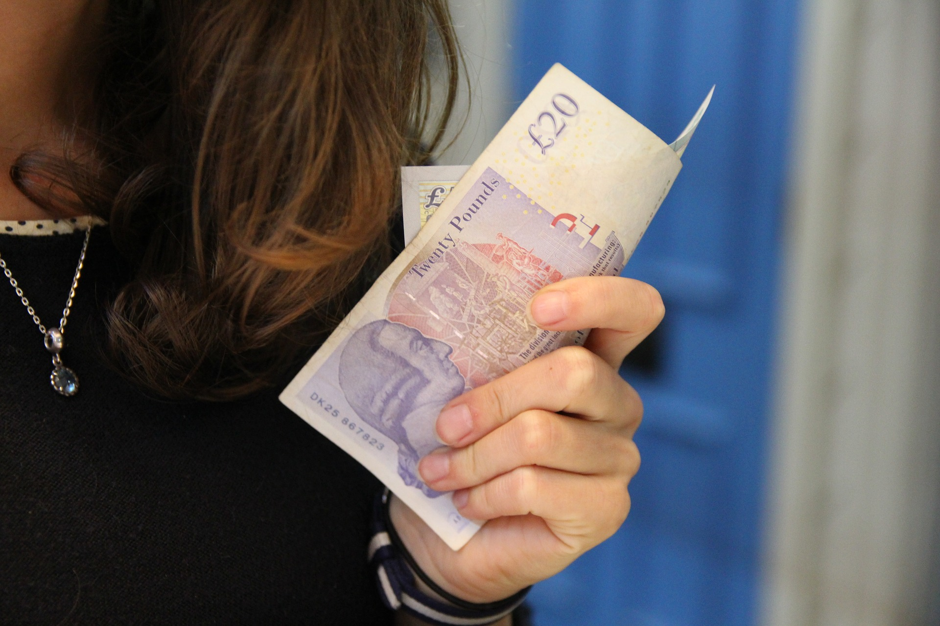Woman holding £20 notes