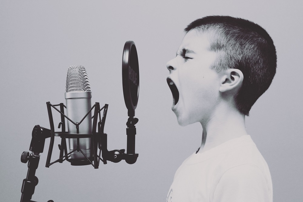 Boy shouting into microphone