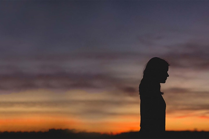woman silhouette over sunset background
