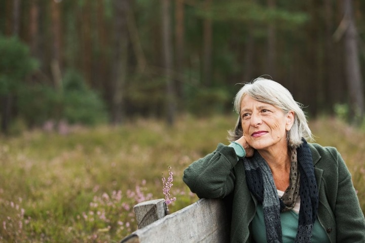 Grey haired woman on park bench