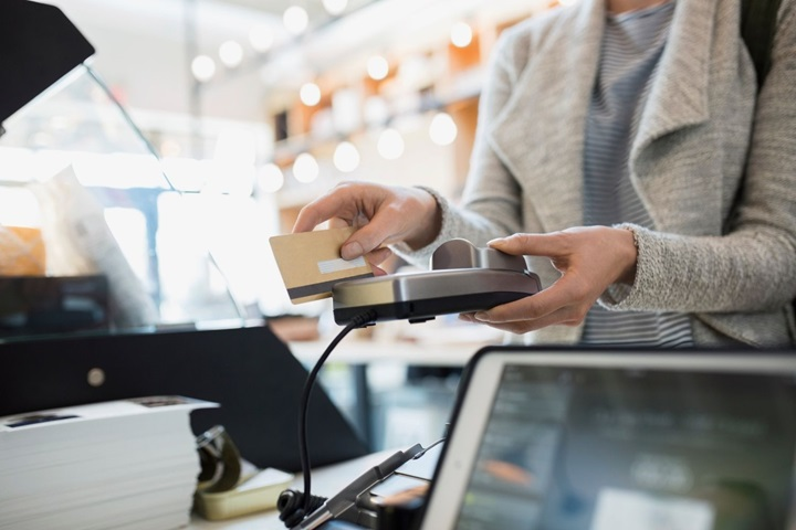 Woman paying with card machine in UK shop