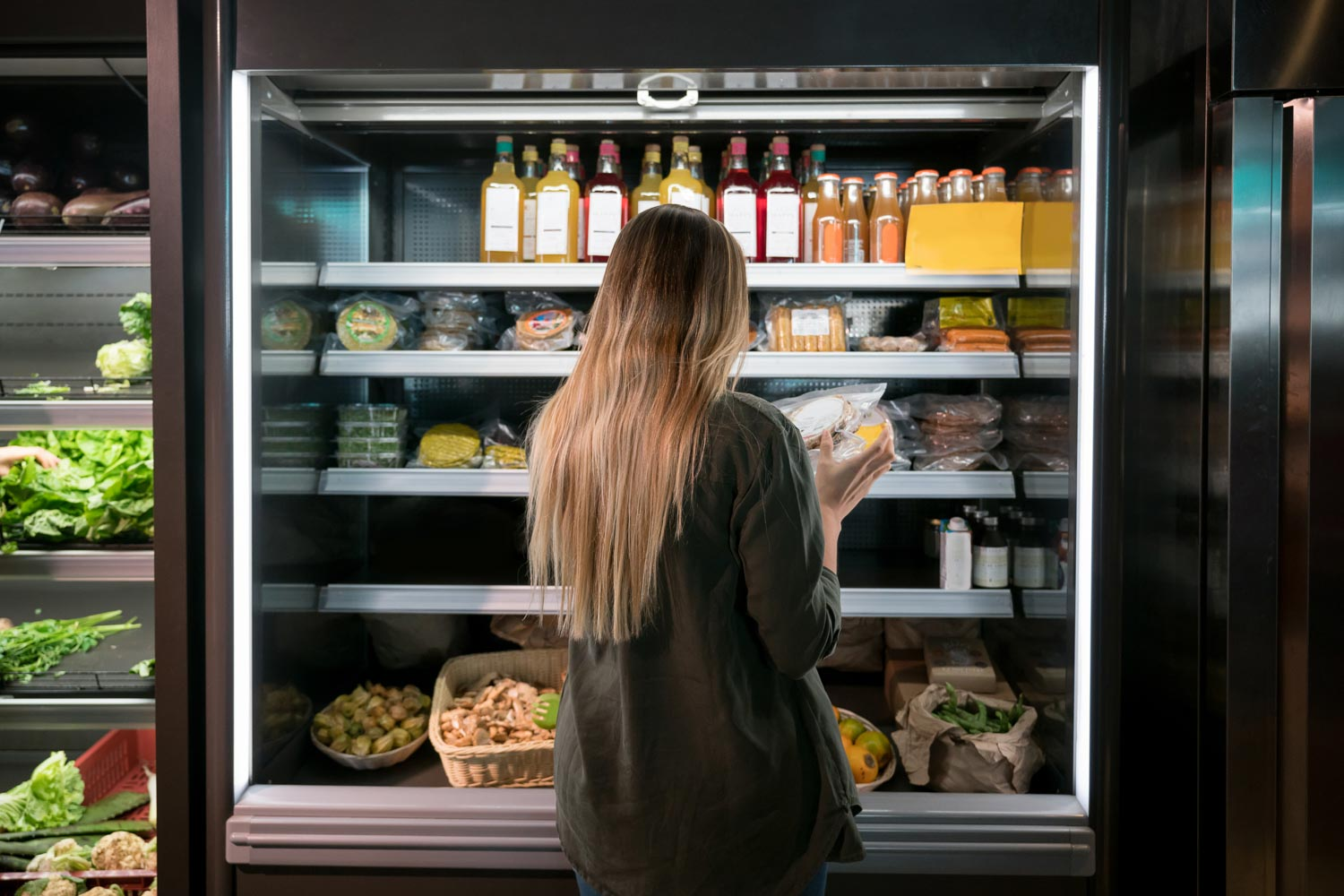 Woman choosing food from supermarket fridge