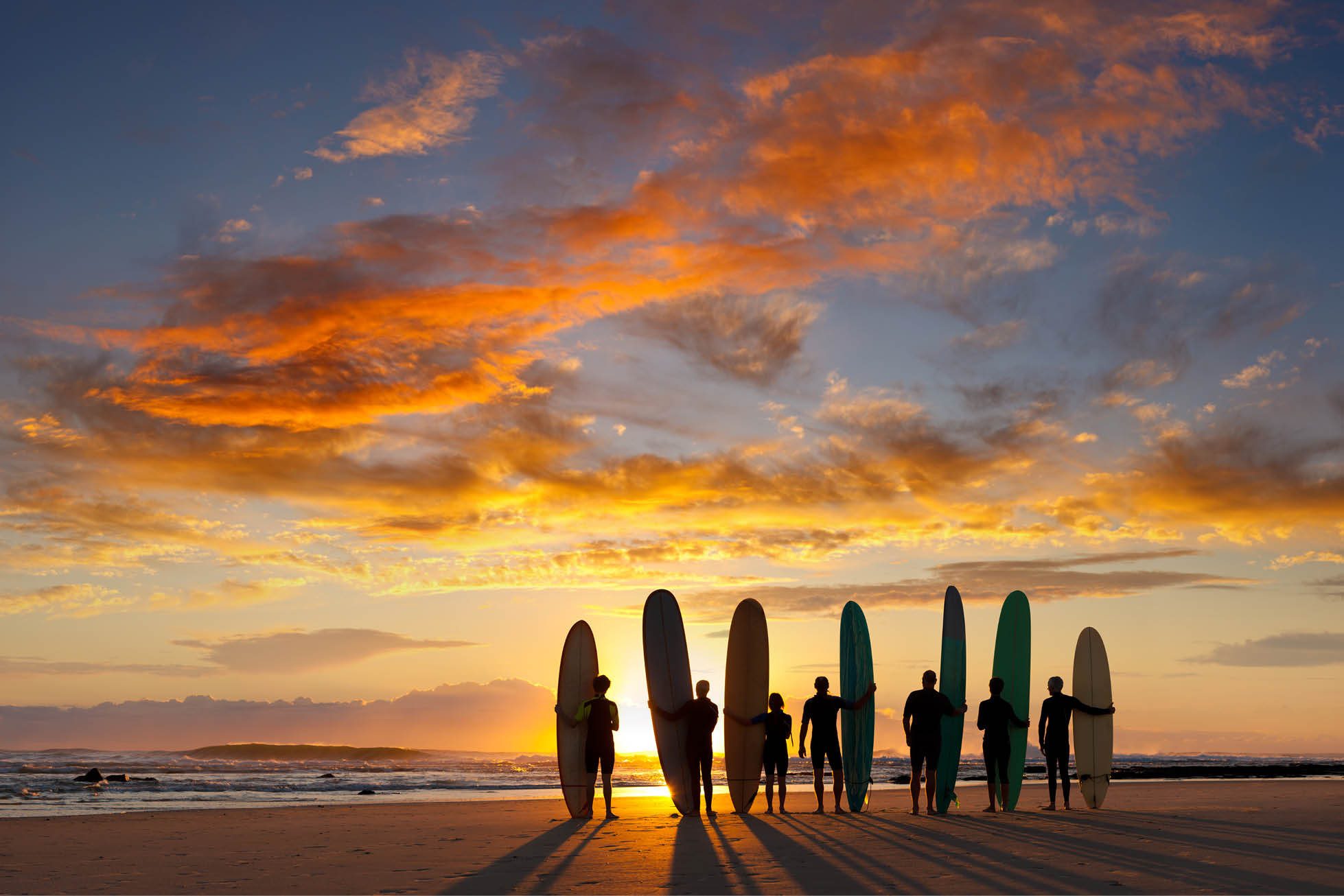 surfers seen against a sunset