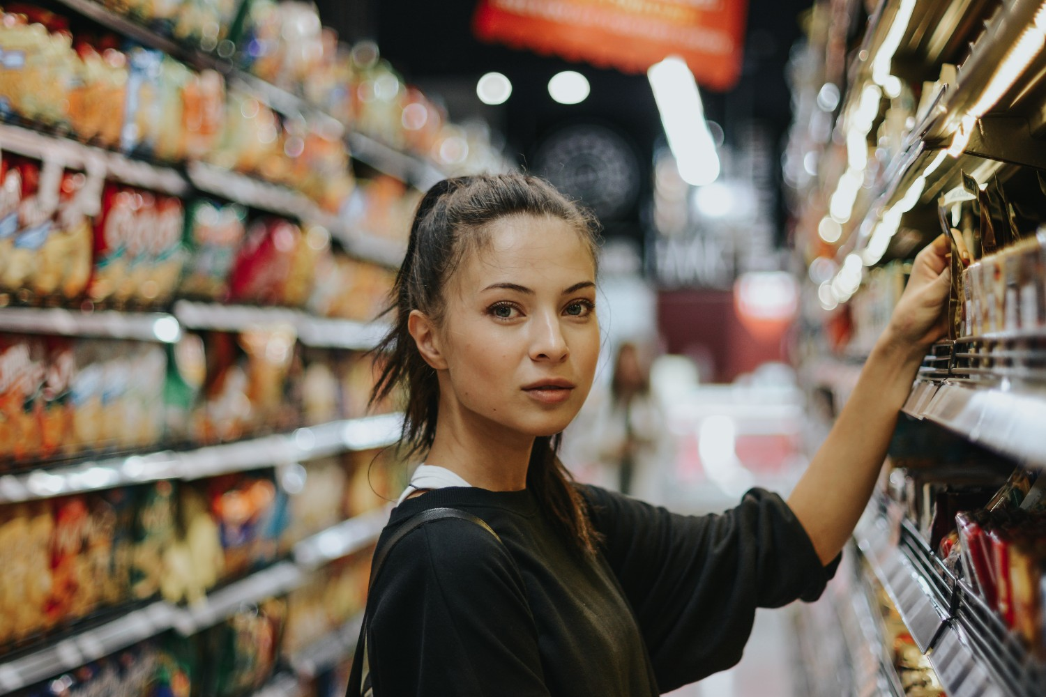 Female shopper selecting product from shelf