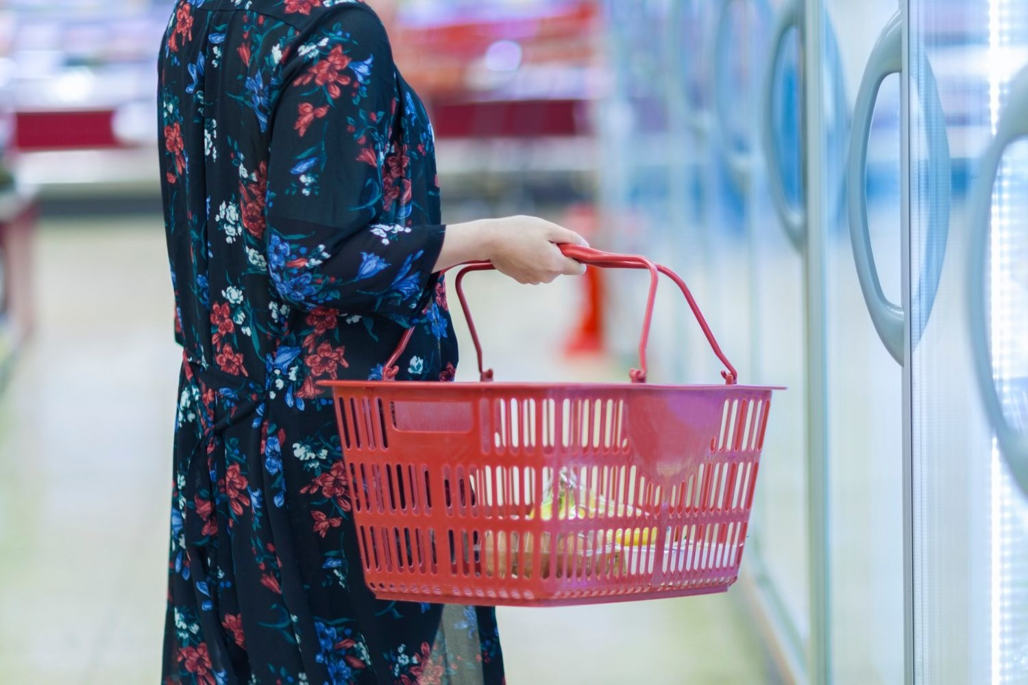 Woman standing in supermarket aisle carrying a red shopping basket
