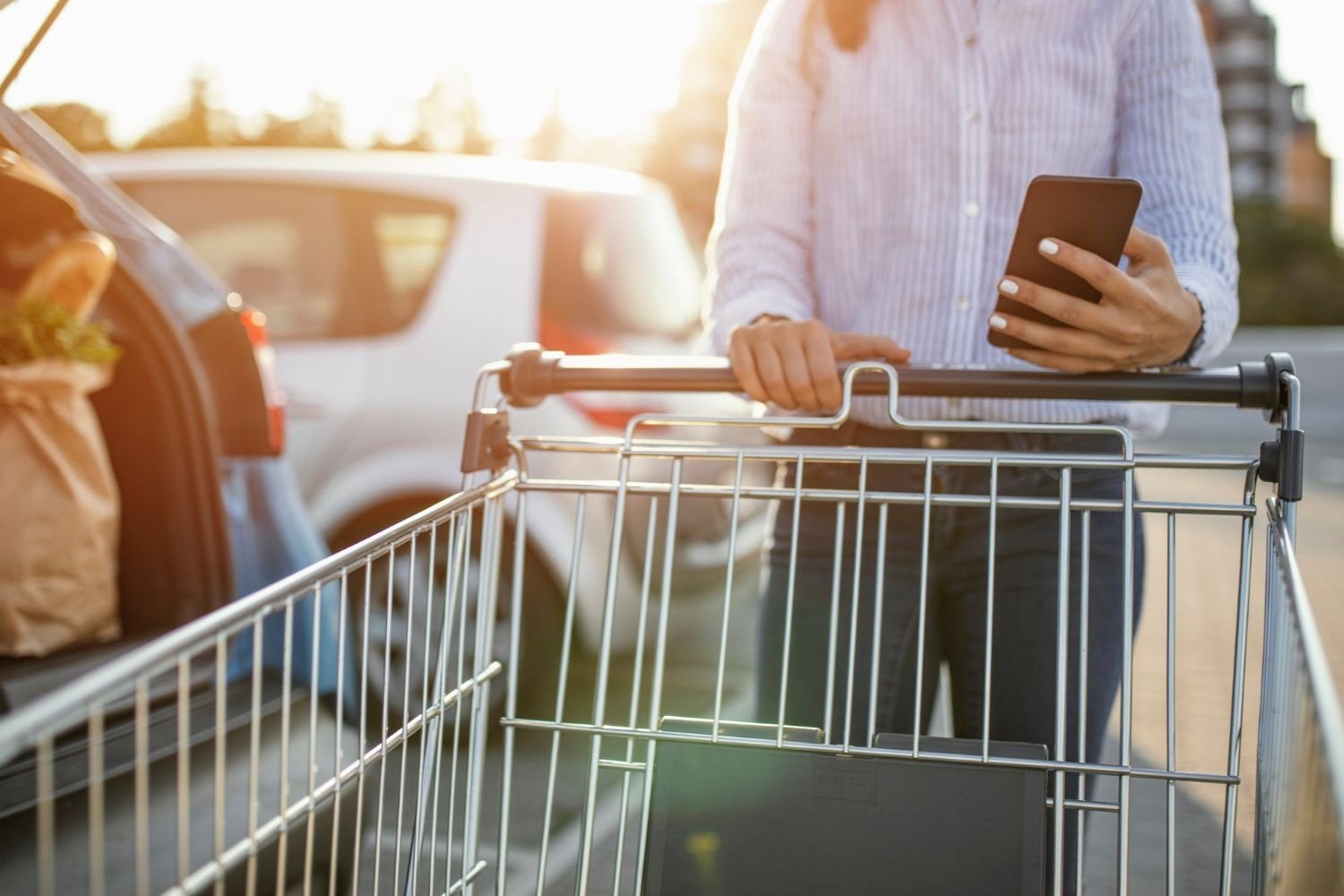 A woman in a white shirt holding a phone while pushing a shopping trolley