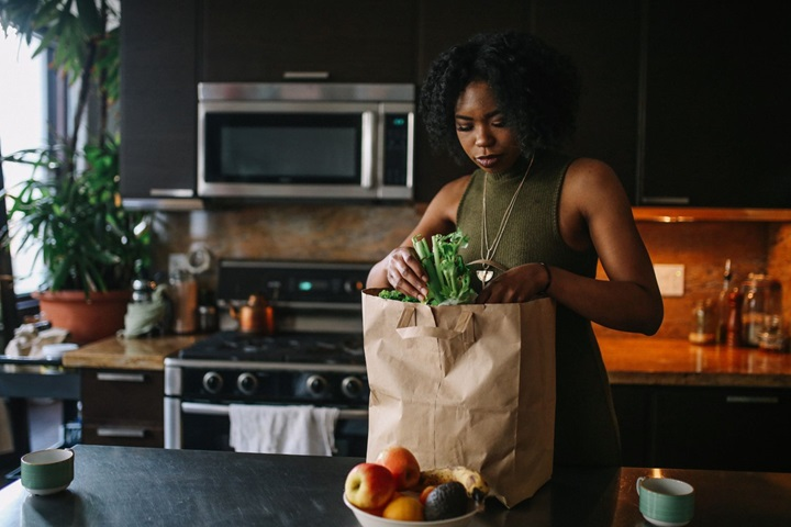 Woman unpacking fruit from a brown paper shopping bag in kitchen